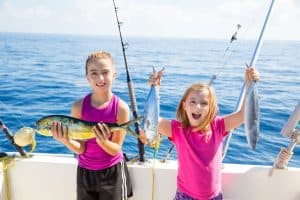 Happy children holding up their catch of fish from deep sea fishing.